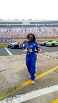 Brenda Jegede on the NASCAR race track with thumbs up.