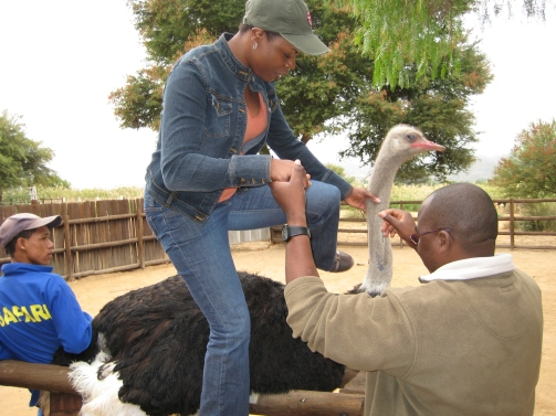 Angenette climbing atop an ostrich for a ride.