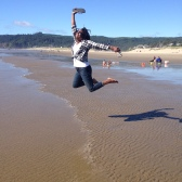 Angenette jumping for joy at the beach.